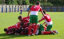 Pile-on: Harrogate Railway celebrate Adam Baker's winning goal with Lawrence Hunter acting as the pile-on co-ordinater